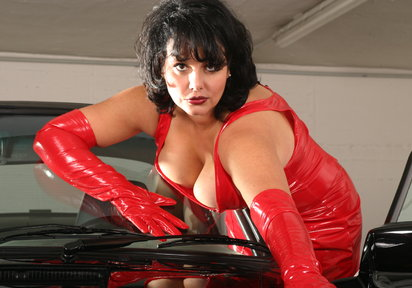 Big tittied and round assed mature lady SisterLove poses in her later red dress and red gloves.
